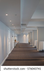 Diminishing perspective of a lobby illuminated with soft light showing white covered round tables, a row of doors and lighting installations. Luxurious carpet on the floor