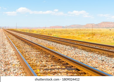 Diminishing perspective of raliway tracks through flat plains of New Mexico with distant mesa landforms under blue sky.