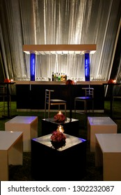 Dimly lit lounge seating area with illuminated drinks bar in the background.