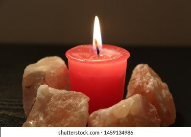 A dimly lit room is illuminated by the small but bright flame of a pink candle.