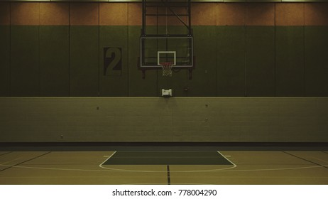 A dimly lit, somber basketball court.