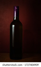 A dimly lit wine bottle on a dark wood table, creating a contrast with the lights that highlight the background and bottle textures