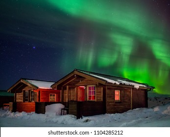 Dimmuborgir, Iceland - February 29, 2016: The Northern Lights (aurora borealis) shimmer over snowy guesthouse chalets in northern Iceland.