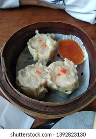 Dimsum or dumplings called siomay with sweet and sour sauce.