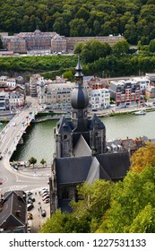 Dinant, Belgium - August 24, 2015 - The top view of The Collegiate Church of Notre-Dame, Charles de Gaulle bridge over Meuse river and Belgian old city houses.