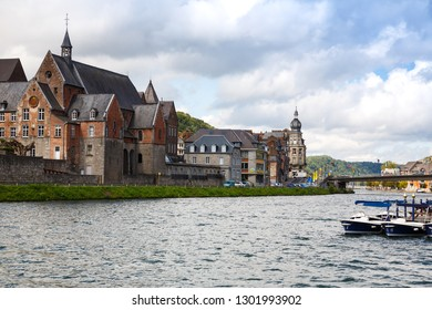 Dinant, Belgium - August 24, 2015 - The houses and church on the coast of Meuse river in Belgian old city.