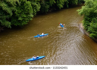 DINANT, BELGIUM. June 17, 2018: Group of friends kayaking on river Semois. People with boats on semoir river near Dinant in Ardennes region, Wallonia, Belgium.