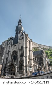 Dinant, Belgium - June 26, 2019: The citadel fort on cliff view is parlty blocked by gray stone Notre Dame church under light blue sky. Fish eye view.