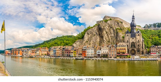 DINANT,BELGIUM - MAY 22,2018 - Panoramic view at the enbankment of Meuse river  with houses and church of Our Lady in Dinant. Dinant is positioned in the Upper Meuse valley.