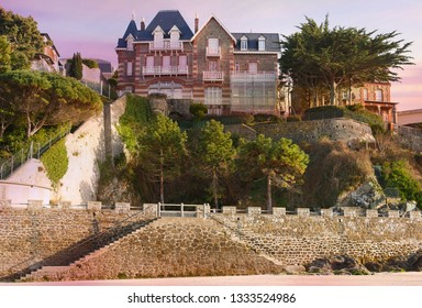 DINARD, FRANCE - March 1, 2019: Beautiful old houses in front of the main beach during sunset. Promenade along the coast, sightseeing and tourism. Brittany, France