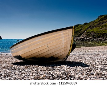 Dinghy or rowing boat beached on pebble beach