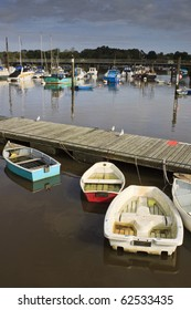 Dingies half filled with water and fishing boats at Lymington Harbor