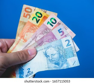 Dinheiro, Brasil, Reais. Real Currency. Person holding money bills and blue background.