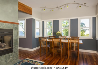 Dining area table and chairs with wood floors, painted walls, accent lighting and view windows in contemporary upscale home interior