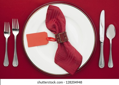 Dining Etiquette with silverware, ceramic plate and place card on a napkin
