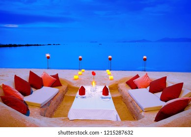 Dining on the beach,Dining table in the sand close to the ocean.dig the sand to do the dining table and over looking to Koh Phangan Samui Thailand