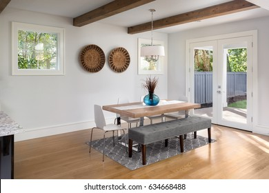 Dining Room in Beautiful Luxury Home with Hardwood Floors, Table,  and Elegant Light Fixture. French Doors lead to Backyard.