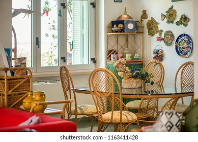 Dining room with big glass table and decorations all around the place. Dried flowers, wicker chairs, clay pottery. Cozy atmosphere at home. concept of waiting the family dinner time