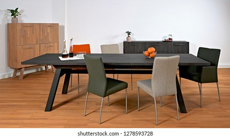 Dining room design with black wooden table and various chairs
