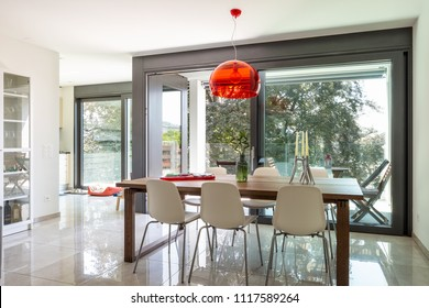 Dining room detail with design table and chairs in modern apartment. Nobody inside