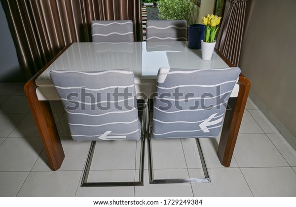 Dining room furniture set. White table with grey motif four chair and yellow tulips flower vase