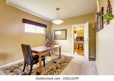 Dining room interior design. Simple wooden table with leather chair on beige rug