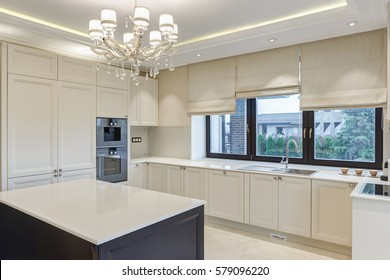Dining room with kitchen bar of the center of room and chandelier over. Room in beige, white and black colors. Big windows with beige jalousie with beautiful view on garden.