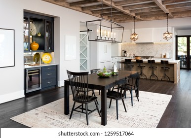 Dining Room and Kitchen In New Farmhouse Style Luxury Home with Elegant Pendant Light Fixtures and Open Concept Floor Plan Design. Features Cross Hatch Wooden Beam Ceiling