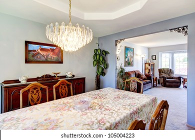 Dining room with a large table and art in an outdated American house.