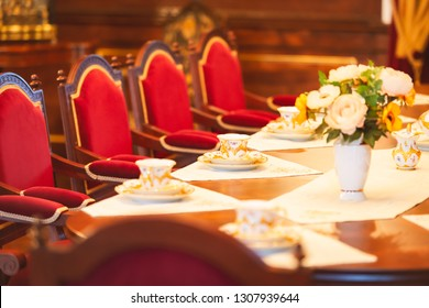 Dining room of medieval castle in Belarus. Old beatiful red chairs and table with flowers