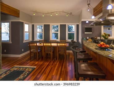 Dining room table and chairs and kitchen breakfast bar with wood floors, granite countertops, accent lighting and view windows in contemporary upscale home interior