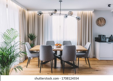 Dining room with wooden table and floor in modern apartment. Interior design - Shutterstock ID 1708124554