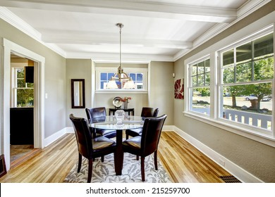 Dining set. Glass round top table with leather chairs. Bright room with windows is perfect for dining area
