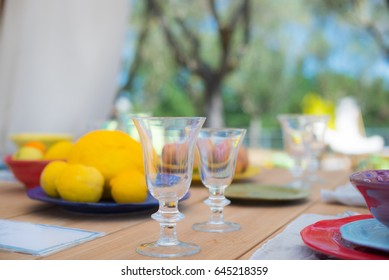 Dining set on outdoor table, focus on glasses, relax and tranquil feeling with lemon fruits in plate in background