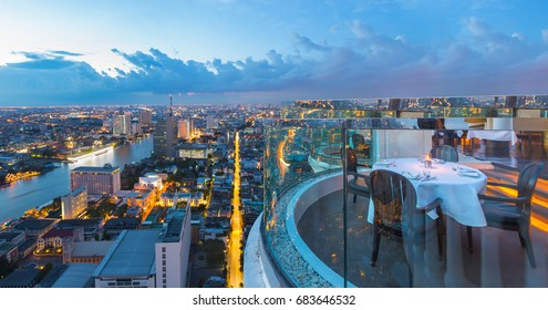 Dining table with beautiful city view on rooftop at twilight scene