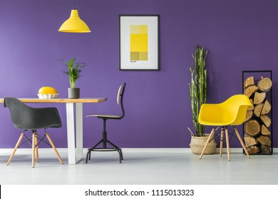 Dining table, black chairs, yellow poster, plants and firewood log rack in a modern dining room interior