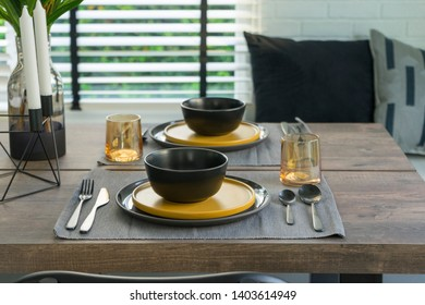 dining table with black and yellow plate setting in modern home.