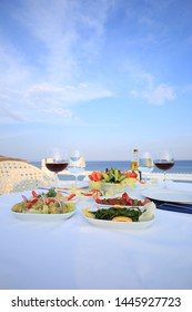 Dining table by the sea with wine and mediterranean food