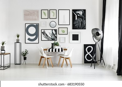 Dining table by the white wall with posters in spacious lounge