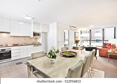Dining table with flower vase near kitchen with sofa, floor is tiled with designs, gas cooker have attached to the wall, flower pot and ceramic plate on the dining table, chair cushion in white color.