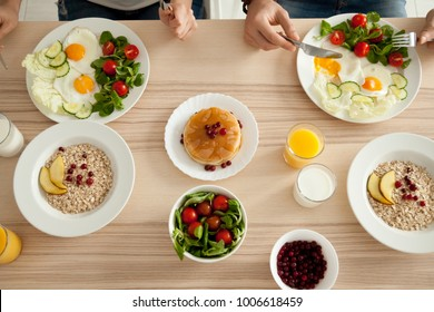 Dining table with food, couple enjoying delicious homemade meal together, man and woman have pancakes, eggs with salad and oatmeal on organic vegetarian breakfast, healthy eating lifestyle, top view