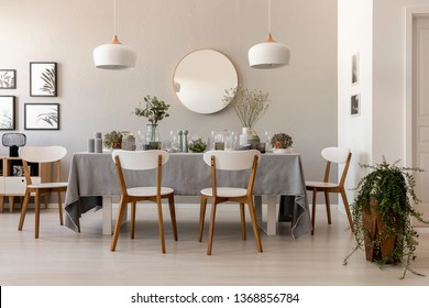Dining table with fresh plants, glass vessels, candles and white chairs in real photo of living room interior with gallery, lamps and mirror on the wall