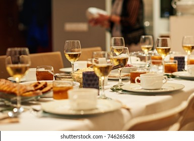 Dining table full of a variety of delicious festive food with a person setting up feast in background