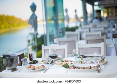 Dining table at river and trees with seafood dishes. Outside dining or lunch concept. Dining and eating in the beautiful nature at open air restaurant. Lunch in nature