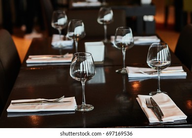 Dining table served with glasses, forks and knifes.