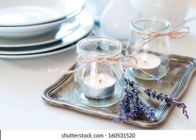 Dining table setting at Provence style, with candles, lavender, vintage crockery and cutlery, closeup.