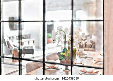 Dining table setup through the glass window view from the outside of a modern house, flower vase can see near ceramic plates, perfect lightning.