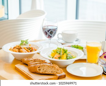 dining table: wine, orange juice, shrimp salad, meat with rice, pasta and coffee