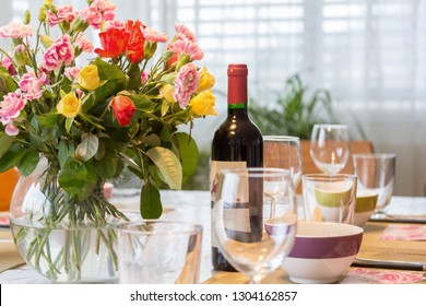 Dining tables with cultery and fresh flowers in a cozy home atomsphere