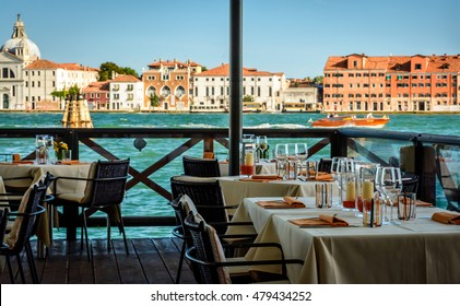 Dining tables in outdoor restaurant and Church of the Santissimo Redentore  in beautiful city Venice
